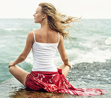 Young blonde woman meditation on the beach